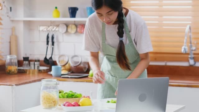young asian woman making salad by learning cooking online from laptop computer, people lifestyles - vegetarian meal stock videos & royalty-free footage