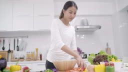 Young Asian woman making salad healthy food in the kitchen, beautiful female in casual use organic vegetables lots of nutrition preparing salad for fit body at home. Healthy food concept.