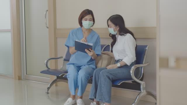 junge asiatische ärztin im gespräch und erklären über medizinische testergebnisse und diagnose mit teenager-mädchen im krankenhaus. - patientin stock-videos und b-roll-filmmaterial