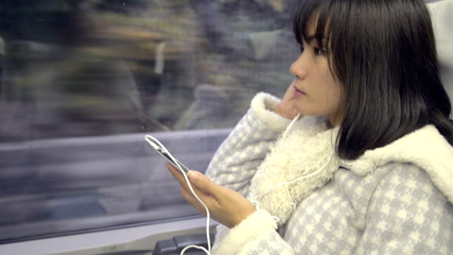 Young Asian Woman on a train Listen to music from her mobile phone