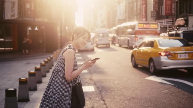 junge asiatische frau bestellt eine ride-aktie per smartphone-app - chinesischer abstammung stock-videos und b-roll-filmmaterial