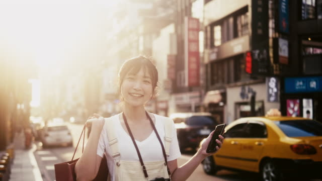 young asian woman orders a taxi via smartphone app - taipei stock videos & royalty-free footage