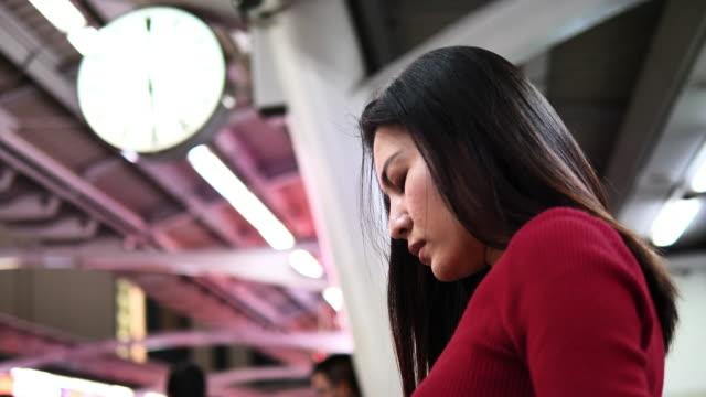 junge asiatische frau passagier mit smartphone-handy - bahnreisender stock-videos und b-roll-filmmaterial