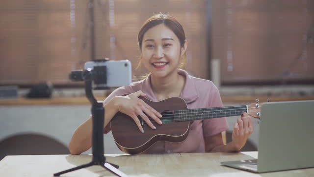 young asian woman play guitar working as influencer, recording vlog and music tutorial live for the internet - musician stock videos & royalty-free footage