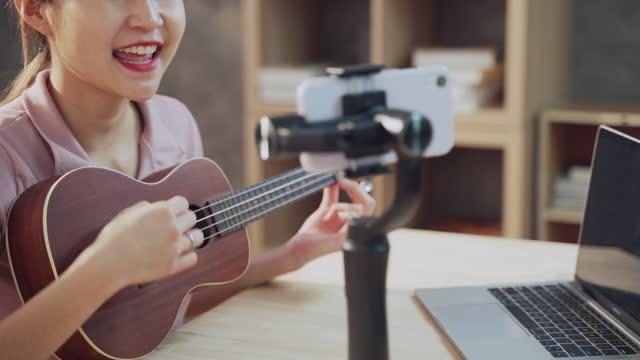 giovane donna asiatica suona la chitarra lavorando come influencer, registrando vlog e tutorial musicale dal vivo per internet - independence video stock e b–roll