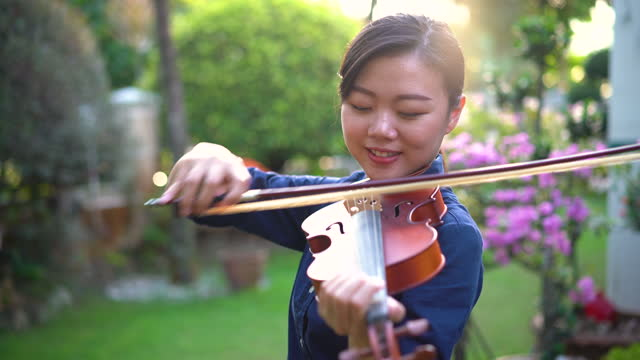 young asian woman playing violin outdoor - violin stock videos & royalty-free footage