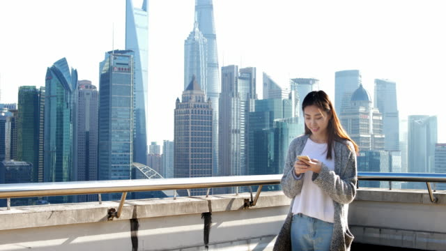 young asian woman plays with mobile phone in modern city - grounds stock videos and b-roll footage