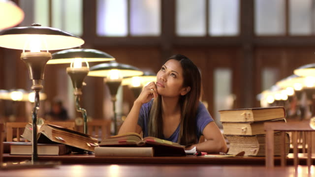 ds young asian woman pondering in the library - ideas stock videos & royalty-free footage