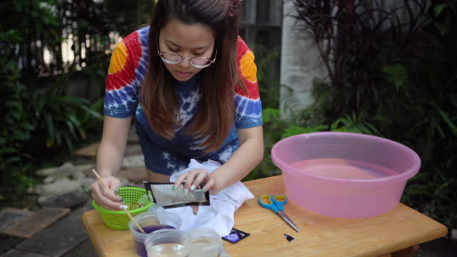 young asian woman practicing to process tie dye fabric on white t-shirt at home , homeschooling concept - dye stock videos & royalty-free footage