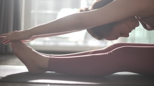 young asian woman practicing yoga at home in morning, slow motion - stretching stock videos & royalty-free footage