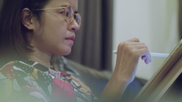グラフィック タブレットを使用創造的なオフィスで若いアジア女性プロのデザイナー - イラストレーター点の映像素材/bロール