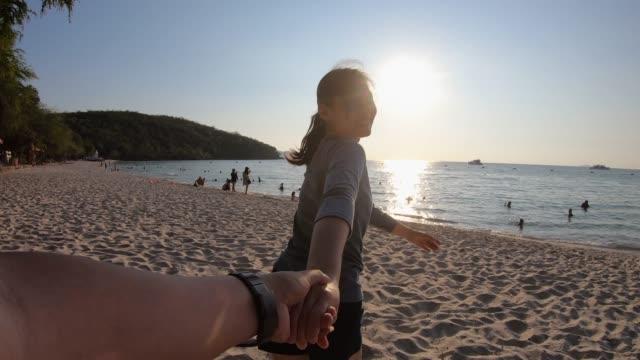 Junge Asiatin zieht ihre Freundin durch den Strand