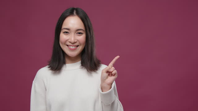 young asian woman raises eyebrows points thumb to marsala copyspace - thumb stock videos & royalty-free footage