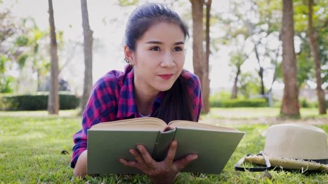 若いアジア女性は本を読んでで公園の外 - ピクニック点の映像素材/bロール