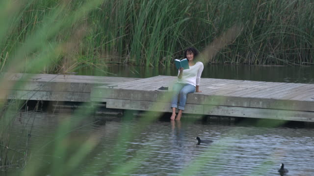 ws young asian woman reading a book by a lake - stagno acqua stagnante video stock e b–roll