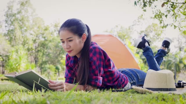 Young Asian woman reading book and laying at outside camping tent, Camping, vacation and travel concept