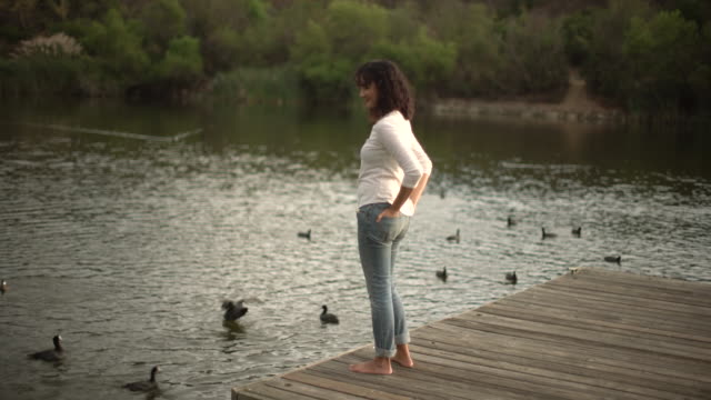 ws young asian woman relaxing by a lake - teich stock-videos und b-roll-filmmaterial
