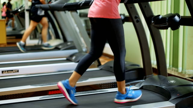 young asian woman running on treadmill in the gym or sport club - treadmill stock videos & royalty-free footage