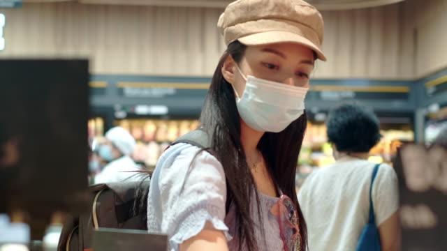 vidéos et rushes de jeune femme asiatique faisant l'achat à l'épicerie - représentation féminine