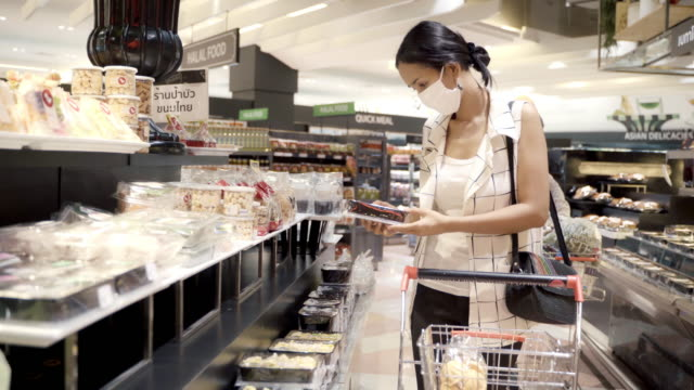 young asian woman shopping at grocery supermarket store and wearing face mask protection from dust and virus for healthy. - food state stock videos & royalty-free footage
