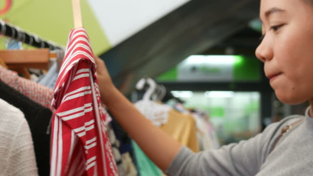 young asian woman shopping at street market - clothes shop stock videos and b-roll footage