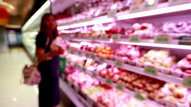 Young asian woman shopping in grocery store, slow motion
