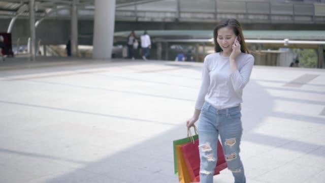 若いアジアの女性は、携帯電話でショッピングします。 - クレジット決済点の映像素材/bロール