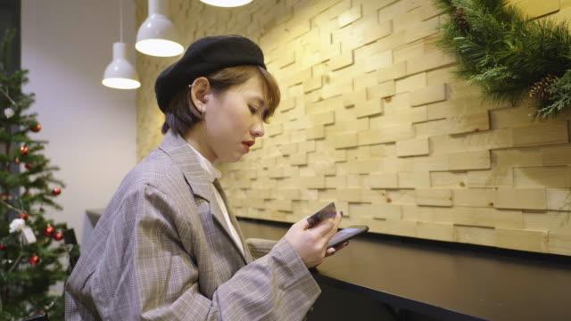 stockvideo's en b-roll-footage met jonge aziatische vrouw die op mobiele telefoon met creditcard winkelt - cadeau