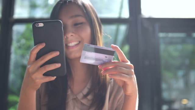 Young Asian woman shopping on mobile phone with Credit card