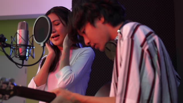 vidéos et rushes de young asian woman singing while man in background playing acoustic guitar. young contemporary sound operator handsome male processing music. recording studio mixing song band concept. - équipement audiovisuel