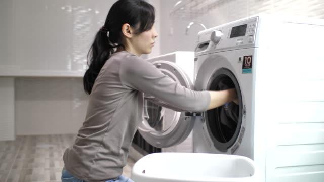 若いアジアの女性は洗濯機の前に座って、汚れた洗濯物で洗濯機をロードします - 電化製品点の映像素材/bロール