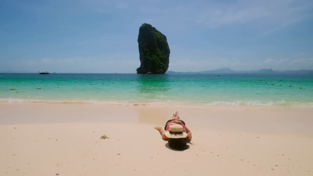 Junge asiatische Frau sitzen und entspannen Sie am wunderschönen Meer entfernt.