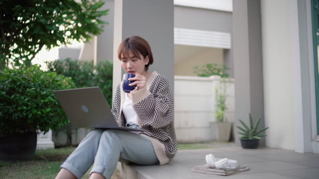 自宅のリビングルームで座って働き、コーヒーを飲む若いアジアの女性 - coffee cup点の映像素材/bロール