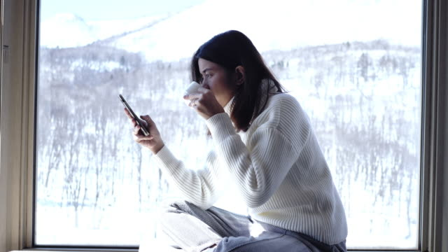 young asian woman sitting in coffee shop using smart phone at snow fall - winter stock videos & royalty-free footage