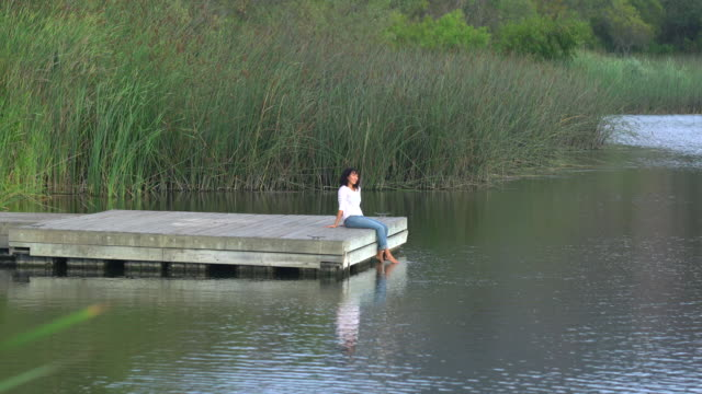 WS Young Asian woman sitting on a dock by a lake
