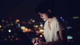 Young asian woman sitting on balcony and working on laptop