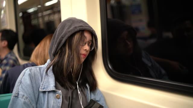 vidéos et rushes de jeune femme asiatique dormant dans un train de métro - passager