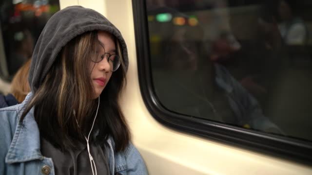 vidéos et rushes de jeune femme asiatique dormant dans un train de métro - passenger train