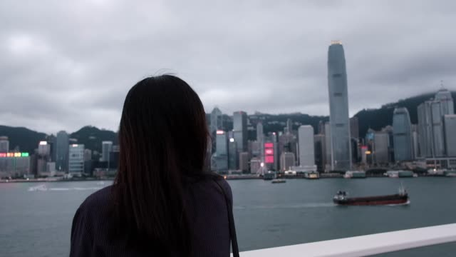 young asian woman standing by the promenade of victoria harbour , looking over hong kong city skyline. panning from the woman to cityscape - asian chance stock videos & royalty-free footage