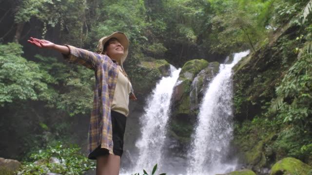 vidéos et rushes de jeune femme asiatique restant par la chute d'eau et embrassant dans le mouvement lent - la vingtaine