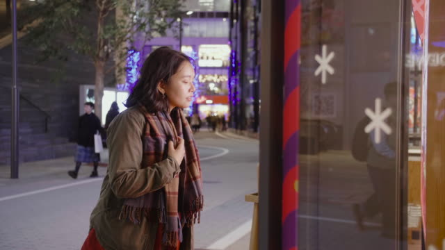 young asian woman standing outside of a store window in the city on a cold night, she are wearing warm clothing. - window display stock videos & royalty-free footage