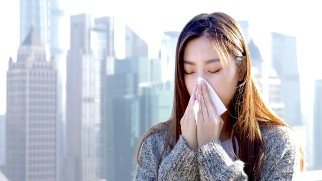 vídeos de stock, filmes e b-roll de jovem mulher asiática fica na cidade moderna - tossindo