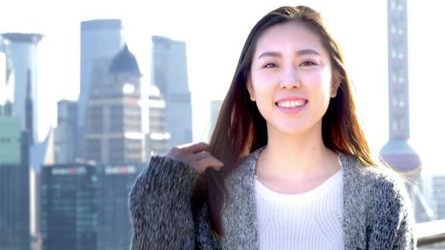 vídeos de stock, filmes e b-roll de jovem mulher asiática fica na cidade moderna - extremo oriente