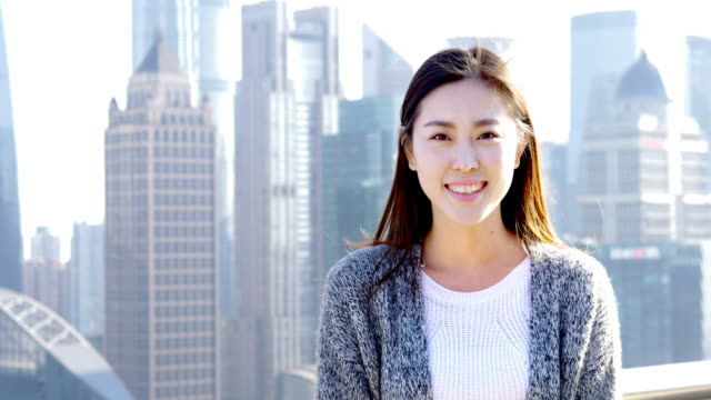 young asian woman stands in modern city