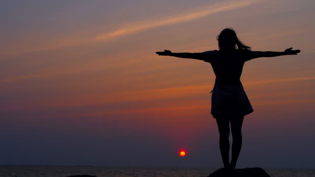 stockvideo's en b-roll-footage met jonge aziatische vrouw uitrekken tijdens yoga pose op strand - lotuspositie