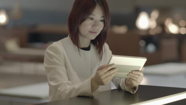 Young Asian Woman Surfing the Internet with Digital Tablet. Text Messaging in a Lobby.