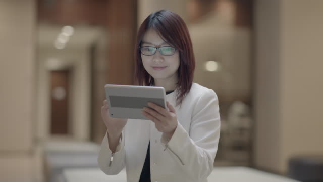 young asian woman surfing the internet with digital tablet. text messaging in a lobby. - mittellanges haar stock-videos und b-roll-filmmaterial