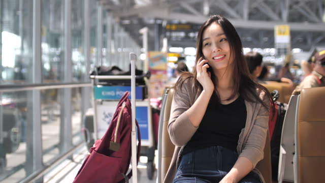 Junge asiatische Frau Gespräch auf ihrer Handy-Flughafen