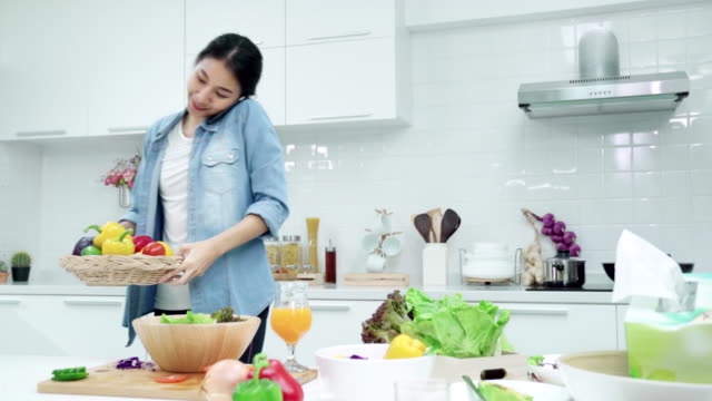 4k uhd : young asian woman talking on the mobile phone and cooking salad at kitchen - recipe stock videos & royalty-free footage