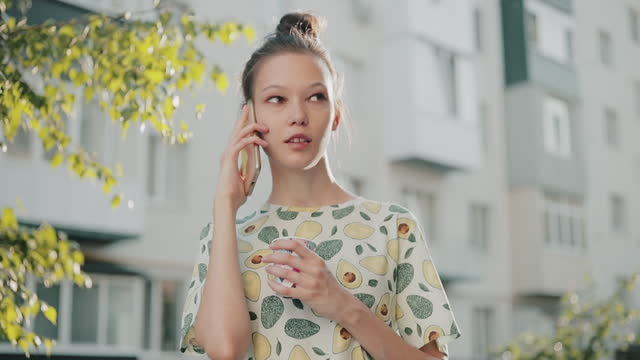young asian woman talking on the phone while holding a plastic cup of coffee outdoors near the wall of an apartment building. - fensterfront stock-videos und b-roll-filmmaterial